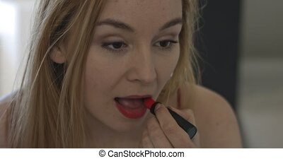 Make up with red lipstick - Close up on mirror reflection of...