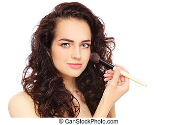 Young beautiful woman applying make-up with big brush, over white background