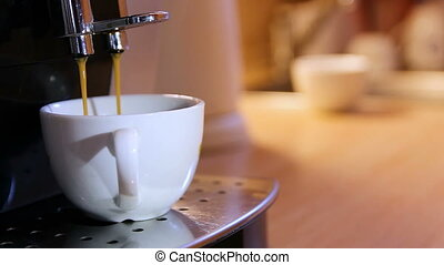 Makeing cup of coffee in coffee maker with blured kitchen background