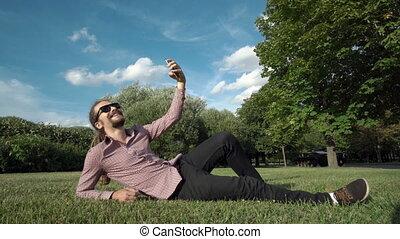 makes selfie in a public park: smart phone, photo