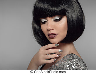 Makeup and Manicure polish nails. Fashionable girl black bob hairstyle. Closeup portrait of Fashion Style Brunette Woman Portrait with black hair and glitter lips isolated on gray background.