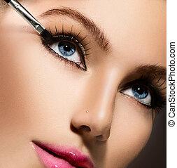 Makeup applying closeup. Eyeliner. Cosmetic eyeshadows