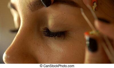 makeup artist adjusts eyebrows young girl with tweezers