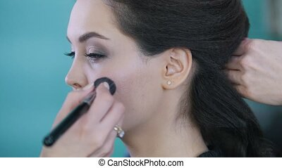 Makeup artist and hairdresser working with client in the...