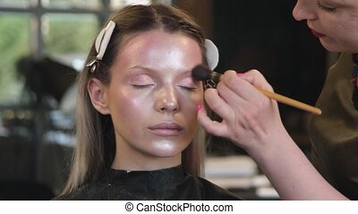 Makeup artist applies cosmetics to face of young woman in ...