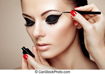 Makeup artist applies eye shadow. Beautiful woman face. ...