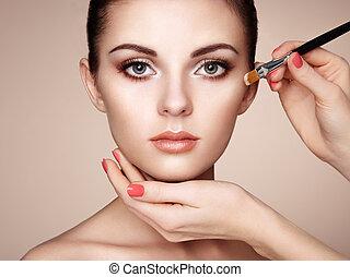 Makeup artist applies skintone. Beautiful woman face. ...