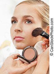 Makeup artist apply blush on cheeks with blush brush