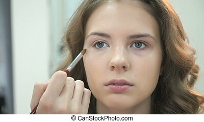 Makeup artist apply make up to young girl