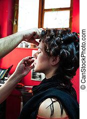makeup artist apply makeup on young woman