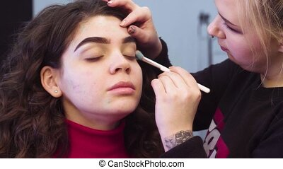 Makeup artist applying eyeshadow - Close up portrait of the...