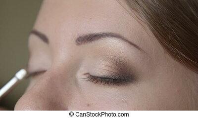 Makeup artist applying eyeshadow closeup
