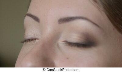 applying eyeshadow closeup - Makeup artist applying...