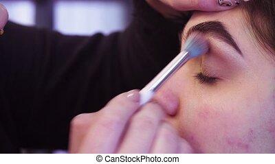 Makeup artist applying eyeshadow - Extreme close up portrait...