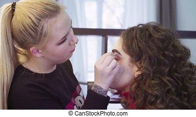 Makeup artist applying eyeshadow - Medium shot portrait of...