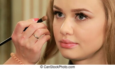 Makeup artist applying eyeshadow on eyelid of a female model