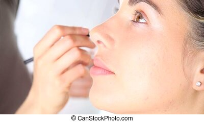 makeup artist applying eyeshadow on eyelid using makeup...