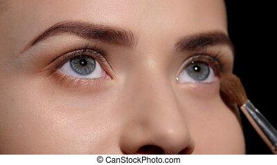Makeup artist applying eyeshadow on eyelid. Black. Closeup -...