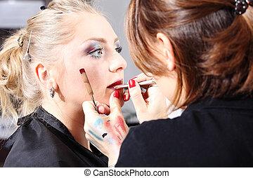 makeup artist applying lipstick on model lips with brush