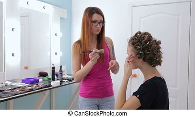 Makeup artist applying liquid tonal foundation on the face of teen girl