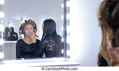 Makeup artist applying liquid tonal foundation on woman's...