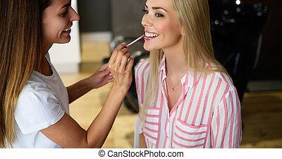 Makeup artist applying liquid tonal foundation on the face...