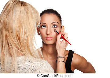 Professional makeup artist applying makeup to model's face - isolated on white
