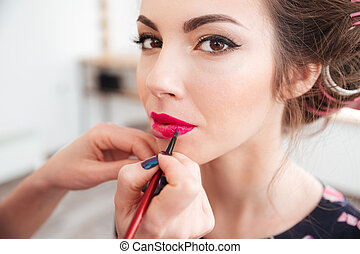 Makeup artist applying pink lipstick to lips of woman