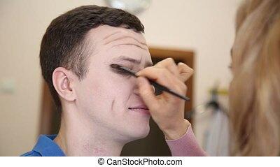 Makeup artist at work. man's make-up.