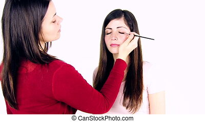 makeup artist at work with model