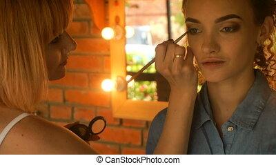 makeup artist carefully paints eyes girl - makeup artist...