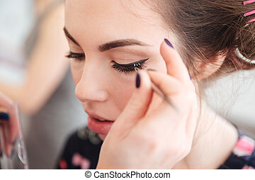 Makeup artist doing false lashes to young woman in curlers -...