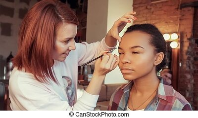 Makeup artist doing make-up beautiful african model.