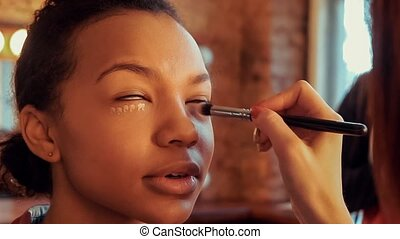 Makeup artist doing make up for young beautiful African model.