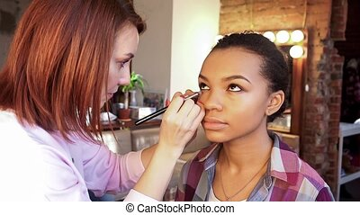Makeup artist doing make-up young beautiful African model.