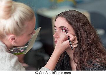 makeup artist doing makeup for a young woman client