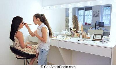makeup artist doing makeup for the beautiful brunette. a...