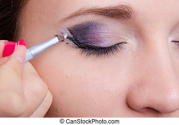 Makeup artist draws arrows on the right eye girl