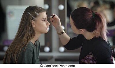 Makeup artist emphasizes the shape of eyebrows model using...