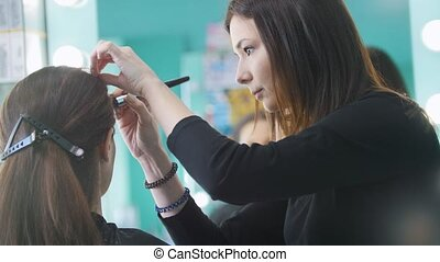 Makeup artist, hairdresser working with client in the beauty salon, shaping eyebrows, fashion and beauty concept