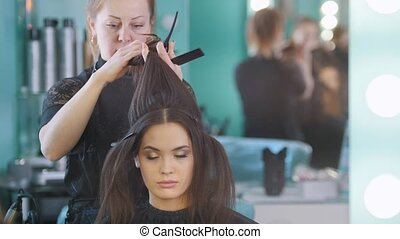 Makeup artist in beauty salon makes hair style for...