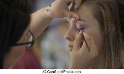Makeup artist is applying eyeliner on eyelid of lady in...