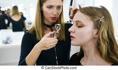 Makeup artist is make up model for show. Young woman...