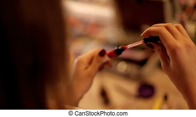 Makeup artist makes a girl beautiful makeup before an important event. girl is sitting in the salon of the make-up artist and she is doing fashionable make-up. Woman putting red lipstick looking in mirror. Makeup at night getting ready before going to party.