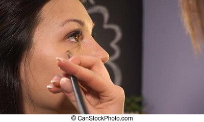 Makeup artist makes makeup for woman model in beauty salon