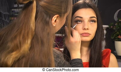Makeup artist makes makeup for woman model