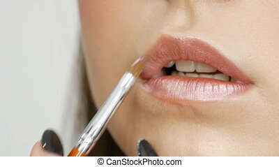 Makeup artist makes makeup girl model. Lipstick light shade applied with a special brush on lips close up view