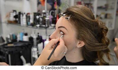 makeup artist makes models eye makeup.