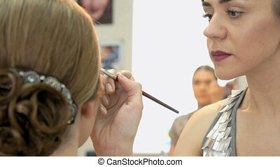 Makeup artist making make-up for stylish model