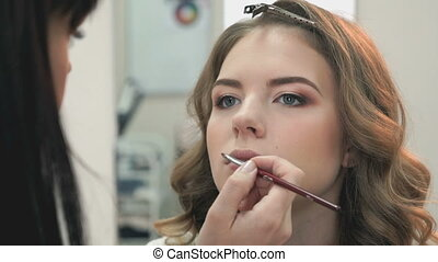 Makeup artist making make-up for stylish model